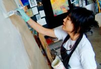 Pauletta painting at the studio.